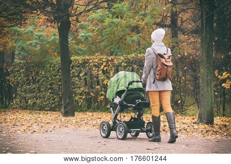 Young mother pushing stroller in autumn park. Young woman strolling with baby in green buggy outdoors