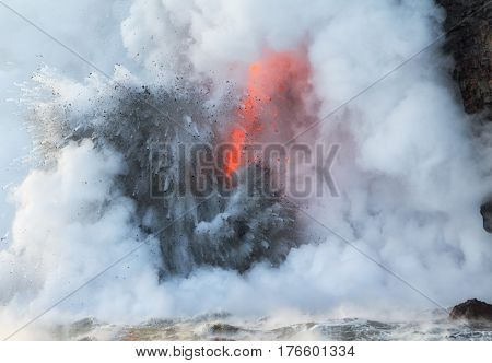 Close up of 'fire hose' lava entering Pacific Ocean at the Kamokuna entry on the Big Island of Hawaii on Feb 1 2017. Ocean steaming hot as molten lava enters ocean. Large explosions throw debris spatter into the air.