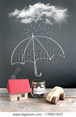 Umbrella sketch on a chalkboard protecting a house car and money