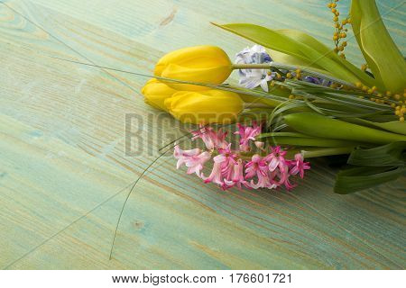 Spring tulips hyacinth over green wooden background