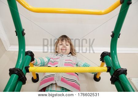 Children home workout. Little girl on gymnastic bar. Child health care and physical development concept. Happy and healthy childhood. Kid on horizontal bar.