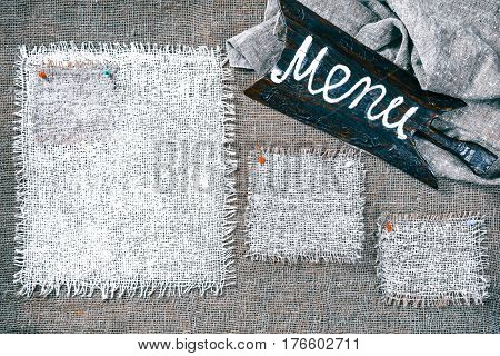 Rectangle pieces of white burlap pinned as various frames on gray burlap background. Wood signboard with text 'Menu' on draped canvas in the corner. Rustic style eco-friendly food template