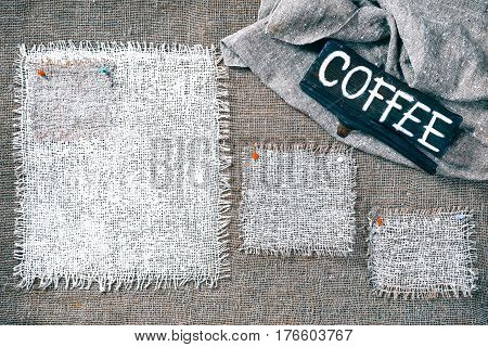Rectangle pieces of white burlap pinned as various frames on gray burlap background. Wood signboard with text 'Coffee' on draped canvas in the corner. Rustic style eco-friendly template