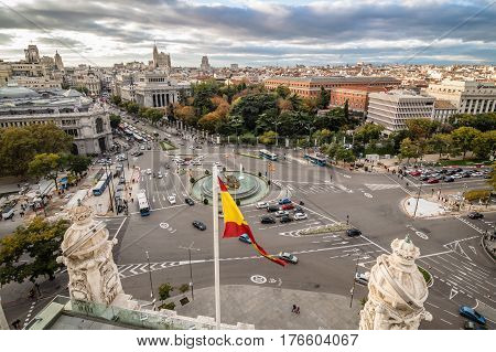 View of Square of Cibeles from Town Hall of Madrid at sunset. Spanish glag on foreground