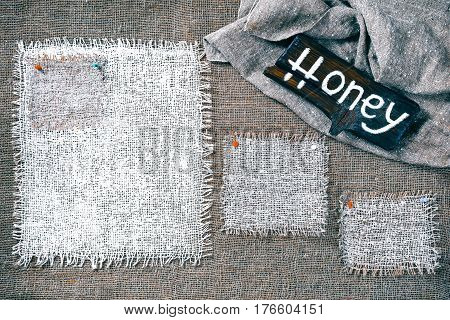 Rectangle pieces of white burlap pinned as various frames on gray burlap background. Wood signboard with text 'Honey' on draped canvas in the corner. Rustic style eco-friendly template