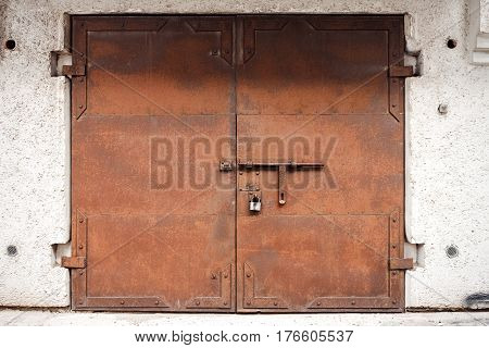 Old rusty metal gate in plaster wall