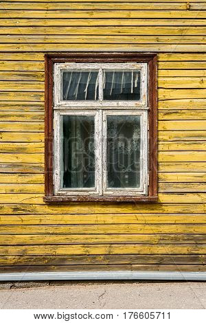 Old window on a aged wooden wall. Architectural detail. Architecture background.