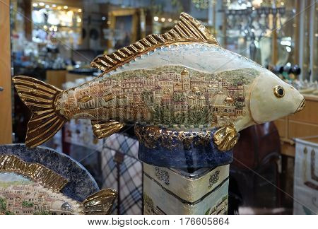 TIBERIAS ISRAEL - FEBRUARY 26 2017: St. Peter's Fish in the window of the souvenir shop. Fish is decorated with a picture of the houses of Jerusalem