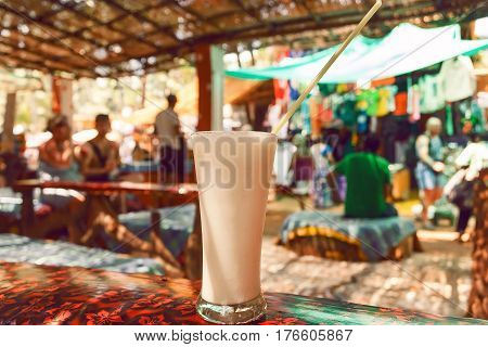 Glass of white creamy milk drink Banana Lassi on table of cafe in Goa, India