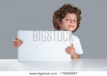 Cute boy put his head on the white box looking at the camera. He is sitting at the table smiling. Gray background. Close-up.
