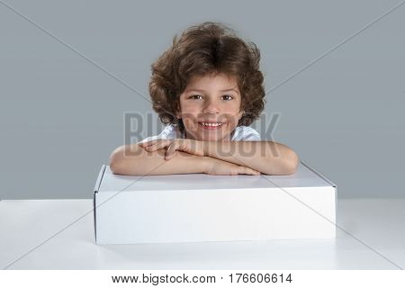 Little boy smiling looking at the camera. Sitting at the table folded hands on the white box. Sad looking at the camera. Gray background. Close-up.