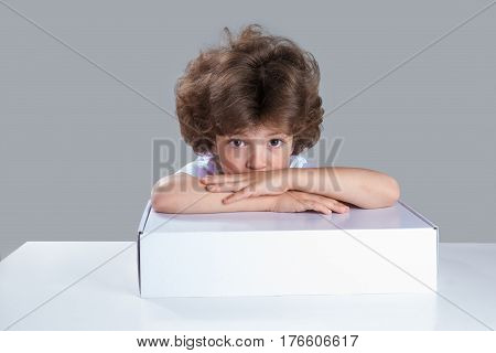 The little boy put his head on his folded hands on the white box. He is sitting at the table looking at camera. Gray background. Close-up.