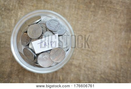 Glass Jar Filled With Coins Labeled With The Words Of The Trip. View From Above. Background Of Burla