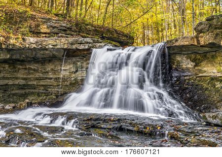 Water cascades over rocky ledges with the woods displaying autumn colors at McCormick's Creek State Park in Indiana.
