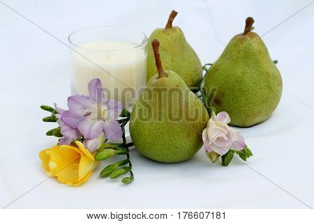 english pear and freesia with votive candle  on a white wooden crate , unusual wedding table or spa  decoration