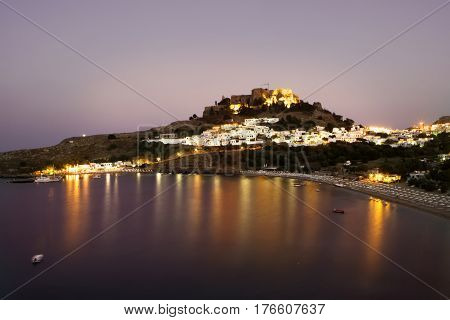 Panoramic view at night of Lindos bay village and Acropolis Rhodes Greece