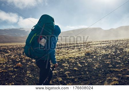 woman hiker on the trail in the Islandic mountains. Trek in National Park Landmannalaugar, Iceland. valley is covered with volcano asher. Dramatic cloudy sky