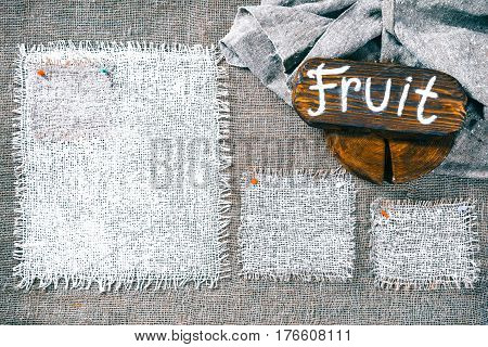Rectangle pieces of white burlap pinned as various frames on gray burlap background. Wood signboard with text 'Fruit' on draped canvas in the corner. Rustic style eco-friendly template