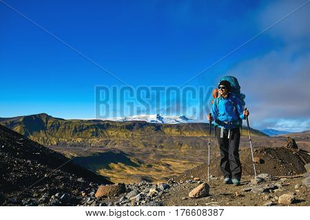 woman hiker on the trail in the Islandic mountains. woman standing and posing against the backdrop of a desert mountain landscape. Treking in National Park Landmannalaugar, Iceland. Travel photography concept