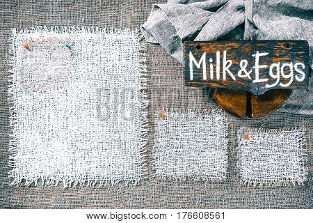 Rectangle pieces of white burlap pinned as various frames on gray burlap background. Wood signboard with text 'Milk and eggs' on draped canvas in the corner. Rustic style eco-friendly template