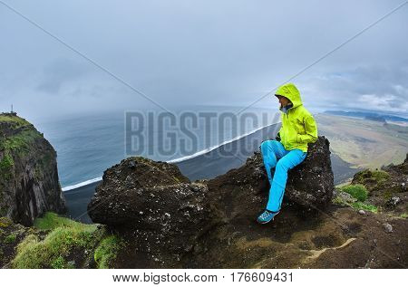 Rreykjavik, Iceland - August 29, 2016: Tourists woman setting on Dyrholaey Cliff Iceland