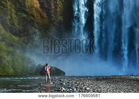 man traveller photographing famous Skogarfoss waterfall in southern Iceland. treking in Iceland. Travel and landscape photography concept