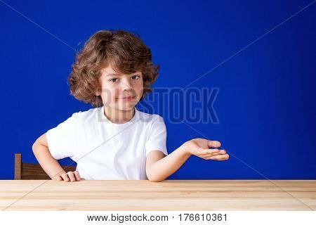 Happy curly cute boy points his hand forward and looking at the camera. Close-up. Blue background.
