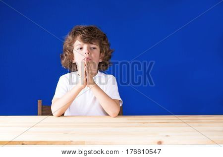 Curly cute boy clasped his hands in prayer and sad looking forward. Close-up. Blue background.