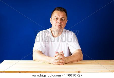 Thoughtful man with folded hands on the wooden table looking at the camera. Blue background.