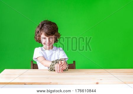 Curly boy with his hands bound by a chain sits laughing and looking in camera. Close-up. Green background.