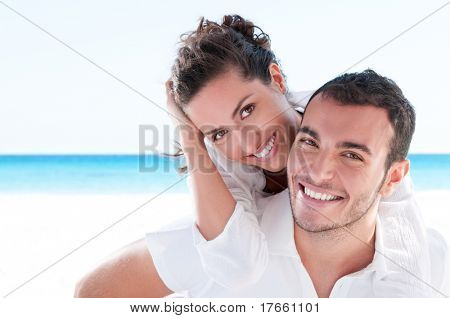 Smiling young couple piggyback at beautiful summer beach