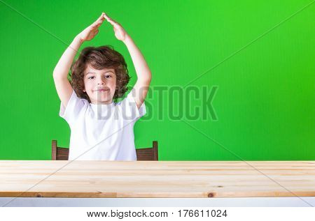 Curly cute boy holding his hands above his head house laughing and looking in camera. Close-up. Green background.