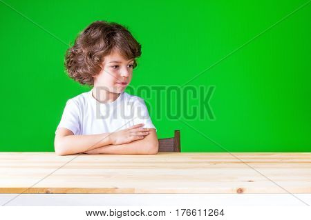 The curly-haired pretty boy with her hands folded on the table looking down turning his head. Sits by the table. Close-up. Green background.