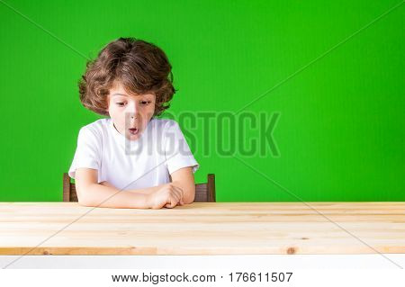Curly resentful little boy sitting with his mouth open looking at the table. Close-up. Green background.
