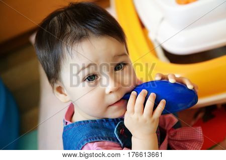 Pretty little girl toddler sitting and eating blue toy mouse