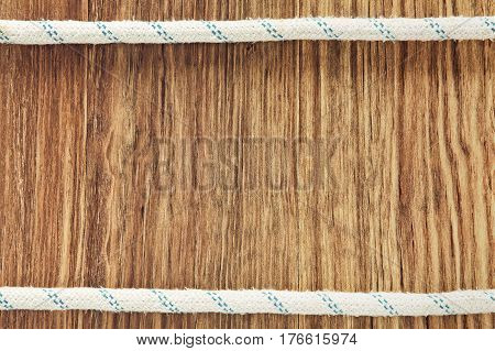 Double rope line on wooden background with empty space for text.