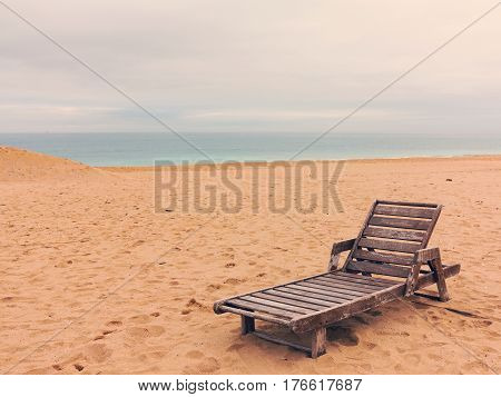Old Wooden Chaise Longue Stands By The Water. Empty Beach.