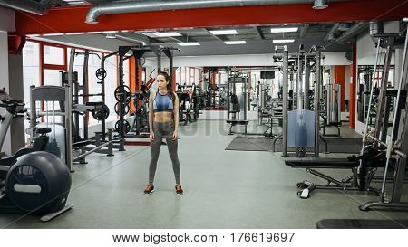 Sporty Woman Standing With Arms Down In Fitness Gym.