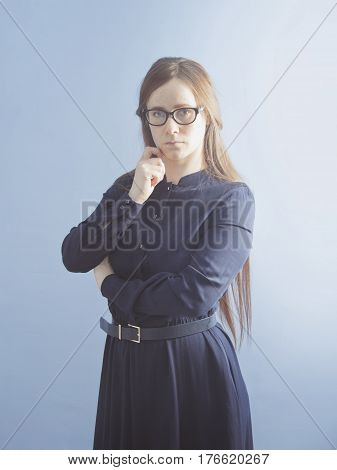 A woman with glasses and a strict dress.