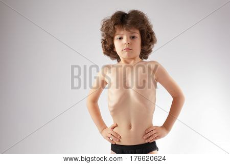 Little curly boy shirtless stomach sucked in and shows her body. Gray background.