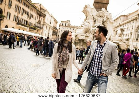 Casual Young Couple Holding Hands Walking In Rome, Italy, Europe