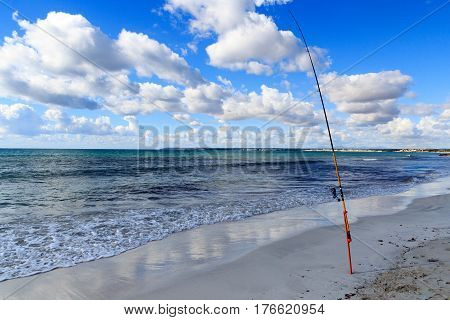 Fishing rod on Platja Es Trenc beach panorama and Mediterranean Sea on Majorca Spain