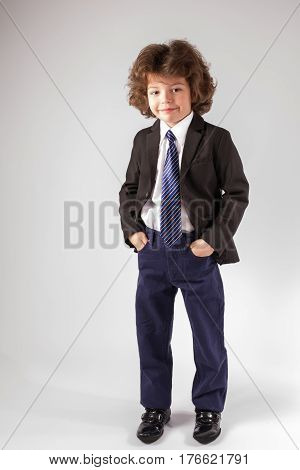 Curly cute boy standing and looking into the camera in an unbuttoned jacket. Gray background.