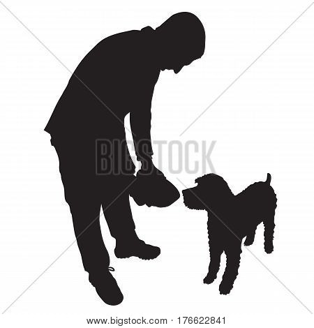 A man is about to feed a dog some food or water from a bowl