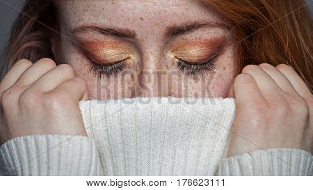 Make up on the eyes of a redhead freckled woman