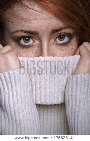 Redhead freckled woman looking out of sweater