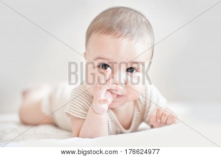 Smiling Newborn Baby Lying On Bed