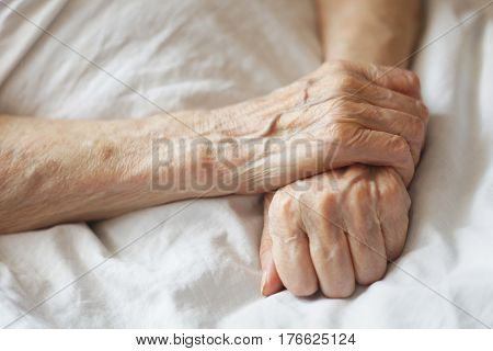 Tired senior's hands on hospital bed. Waiting for a medicine.