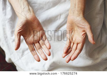 Tired senior's hands on the bed. Hospital time