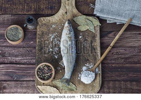 Fresh smelt fish on the kitchen board around spices and salt
